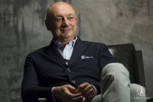 Designer, Piero Lissoni smiles in his chair.
